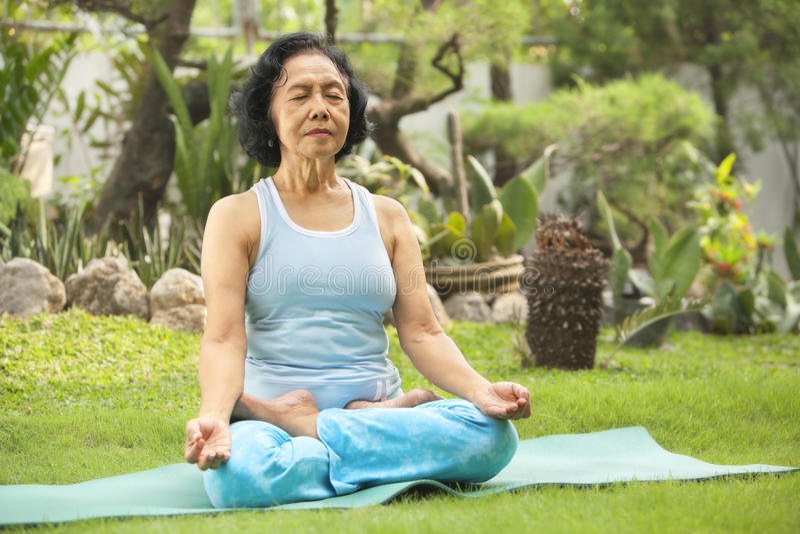 Asian senior woman meditating for yoga outside royalty free stock photos
