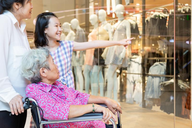 Asian senior woman or mother with her daughter and smiling of child girl or granddaughter looking at shop in shopping mall stock image