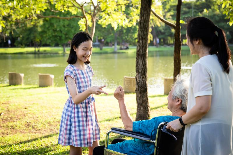 Asian senior woman playing rock paper scissors game,having happiness,smiling with her daughter and granddaughter on wheelchair at royalty free stock photography