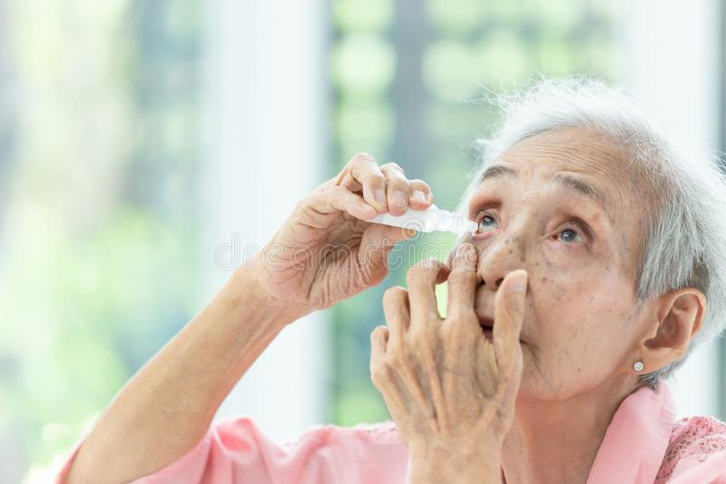 Asian senior woman putting eye drop,closeup view of elderly person using bottle of eyedrops in her eyes,sick old woman suffering stock photos