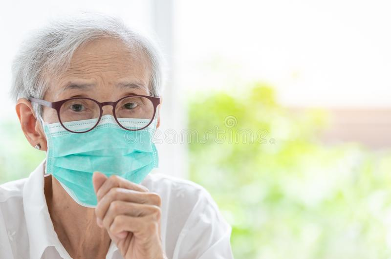 Asian senior woman suffer from cough with face mask protection,elderly woman wearing face mask because of air pollution,Sick old stock image