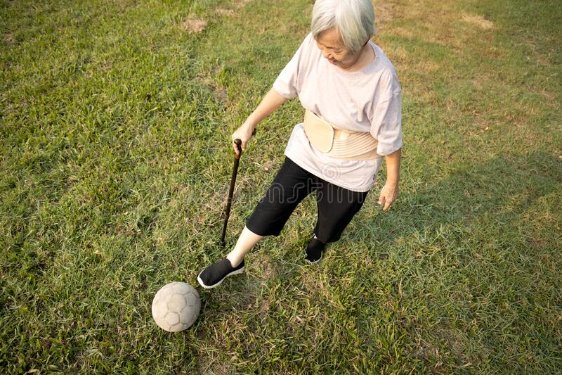 Asian senior woman with walking stick,playing with old football,healthy female elderly is kicking soccer ball,physical exercise, stock photography