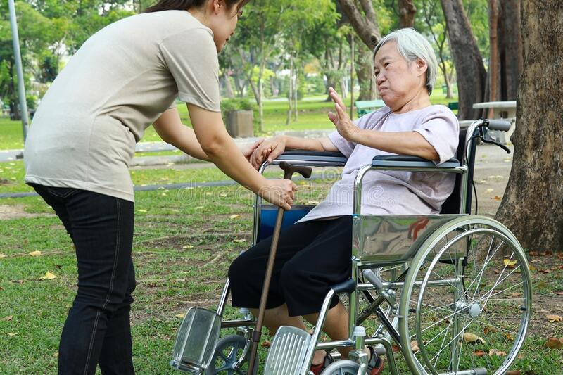 Asian senior woman who refuses to walk,female elderly afraid of getting up from wheelchair,old people fear of falling,geriatric royalty free stock image