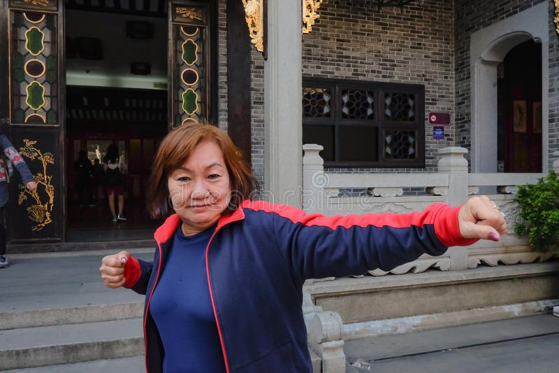 Asian senior women Traveler make a Kung fu pose in front of Wong Fei-hung Memorial Hall. Asian senior woman Traveler make a Kung fu pose in front of Wong Fei royalty free stock photography