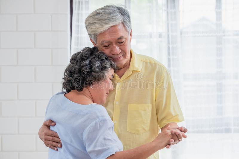 Asian seniors couple enjoy dancing in living room at home.aging at home concept stock photography