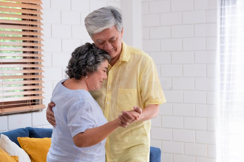 Asian seniors couple enjoy dancing in living room at home.aging at home concept.  royalty free stock photo