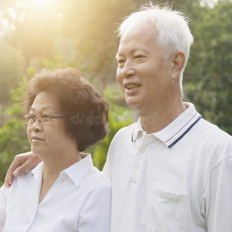 Asian seniors couple looking away. Portrait of healthy Asian seniors retiree couple looking away at outdoor nature park, morning beautiful sunlight background stock image