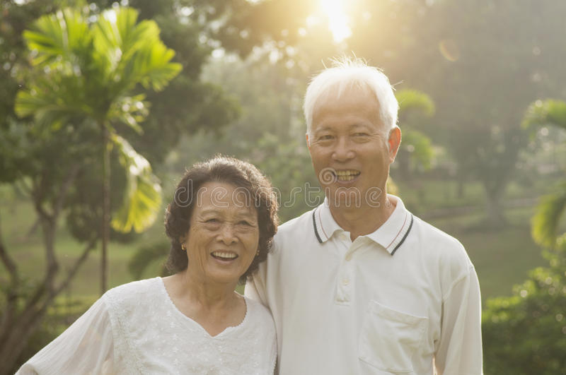 Asian seniors couple at outdoor. Portrait of healthy and happy Asian seniors retiree couple having activities at outdoor nature park, morning beautiful sunlight royalty free stock photography