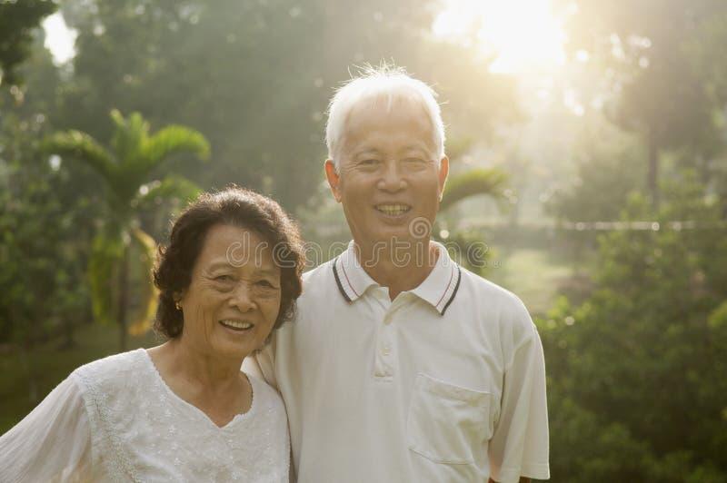 Asian seniors couple at park. Portrait of healthy Asian seniors retiree couple having activities at outdoor nature park, morning beautiful sunlight background stock image