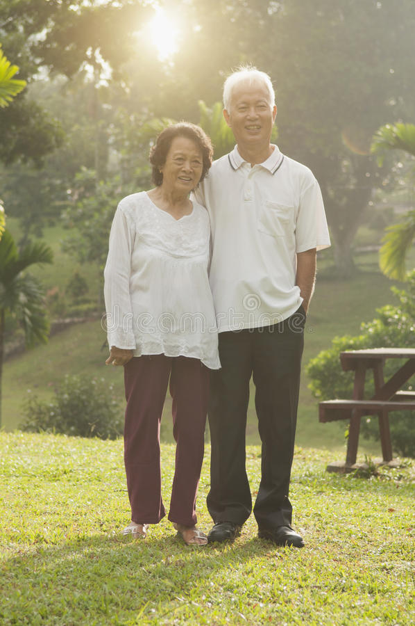 Asian seniors couple walking at outdoor park stock photography