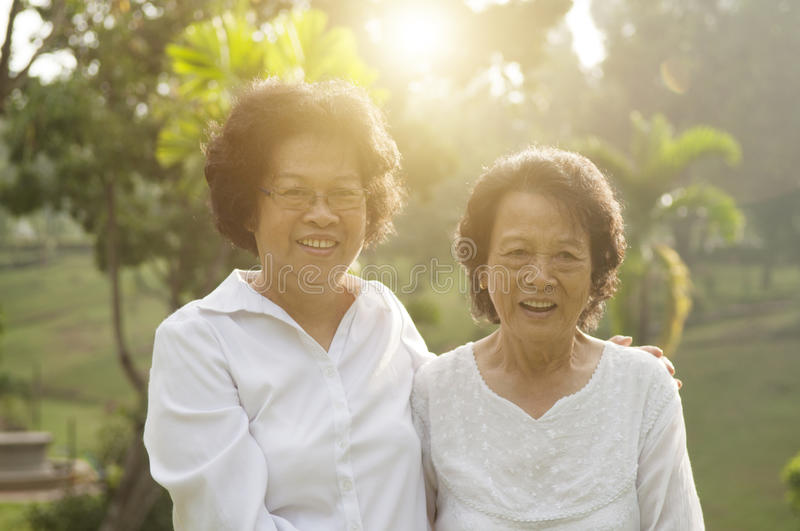 Asian seniors family having fun. Portrait of healthy Asian seniors mother and daughter relaxing at outdoor nature park, morning beautiful sunlight background stock images