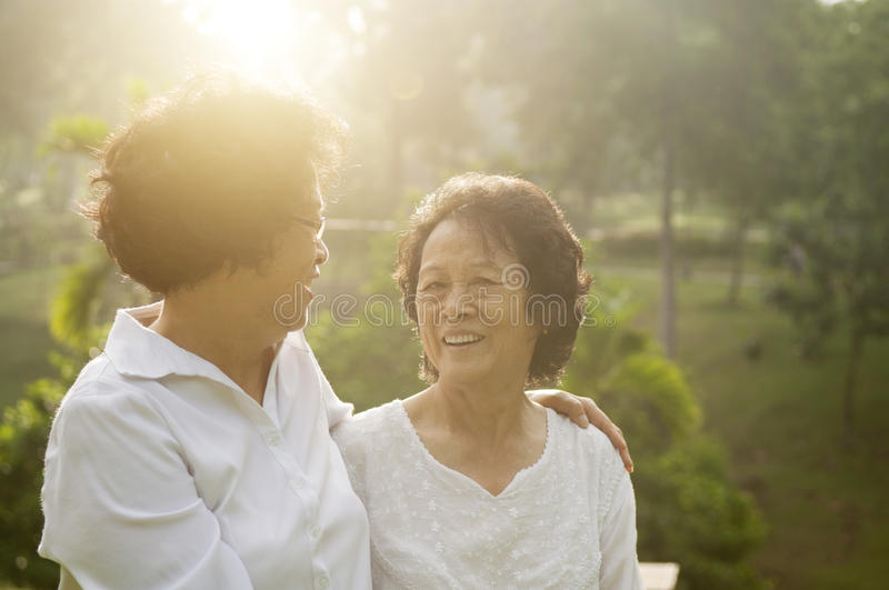 Asian seniors family at outdoor. Portrait of healthy Asian seniors mother and daughter having fun at outdoor nature park, morning beautiful sunlight background stock photography
