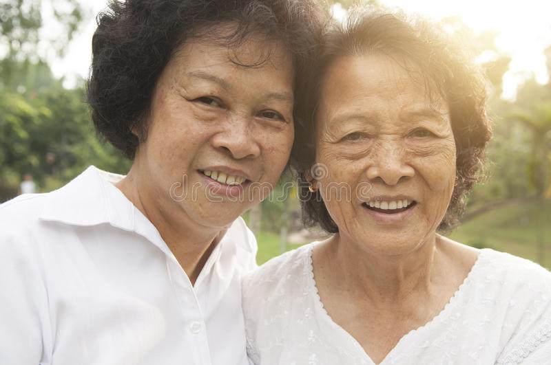 Asian seniors family smiling outdoor. Portrait of healthy happy Asian seniors mother and daughter having fun at outdoor nature park, morning beautiful sunlight royalty free stock photography