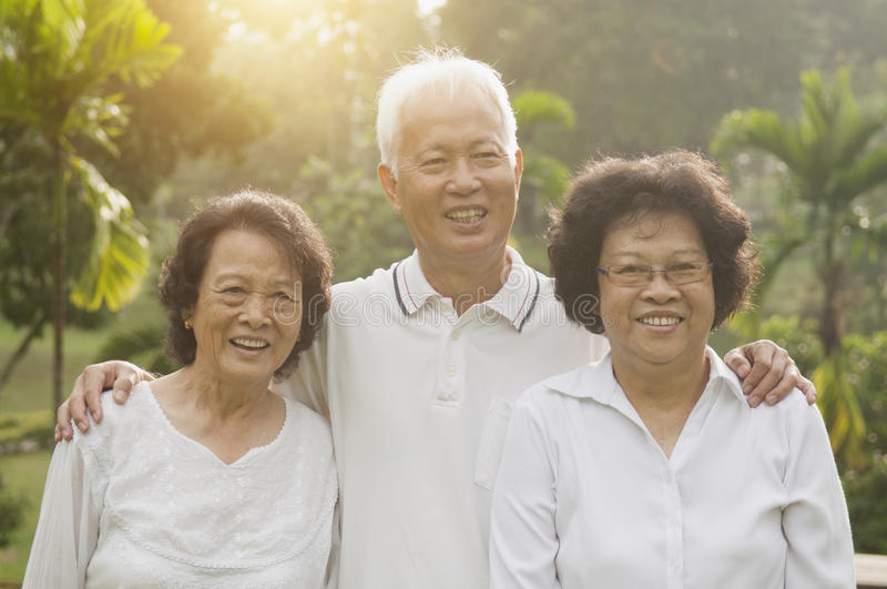 Asian seniors group at outdoor park. Group of healthy happy Asian seniors celebrating friendship at outdoor nature park, in morning beautiful sunlight at stock images
