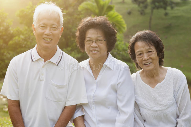Asian seniors group portrait. Portrait of healthy Asian seniors group having fun at outdoor nature park, in morning beautiful sunlight at background royalty free stock photo
