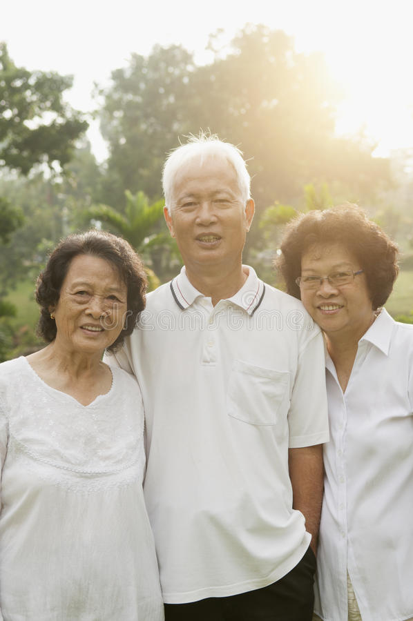Asian seniors group smiling. Group of healthy happy Asian seniors enjoy retired life at outdoor nature park, in morning beautiful sunlight at background stock image