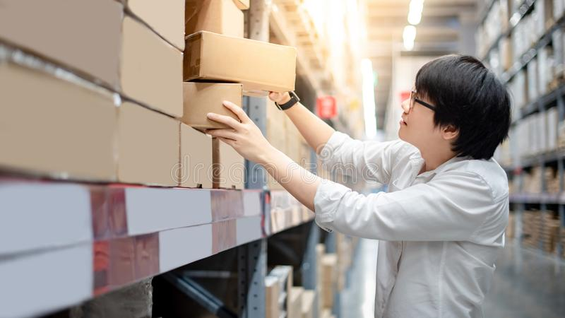 Asian shopper picking cardboard box in warehouse. Young Asian shopper man picking cardboard box package from product shelf in warehouse. Male customer shopping royalty free stock image