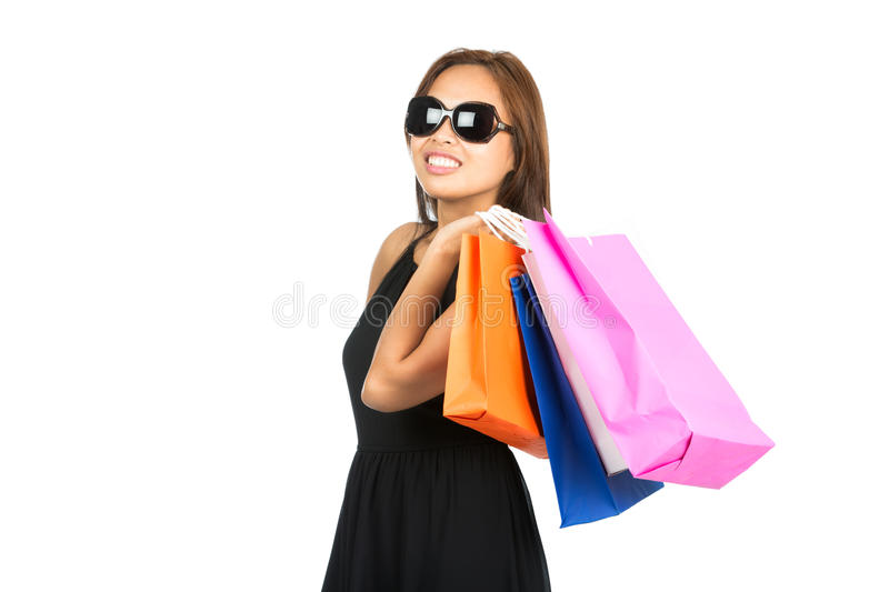 Asian Shopping Bags Flung Over Shoulder Look Away. A cute Asian female shopaholic in sunglasses, stylish black dress has fun with colorful department store stock images