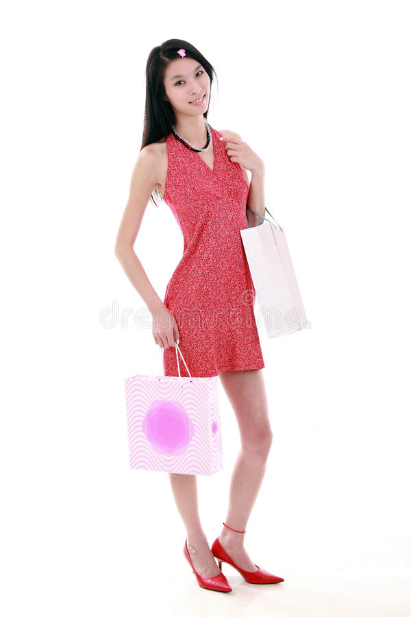 Asian shopping girl. A beautiful Asian girl holds two shopping bags on white background royalty free stock photo