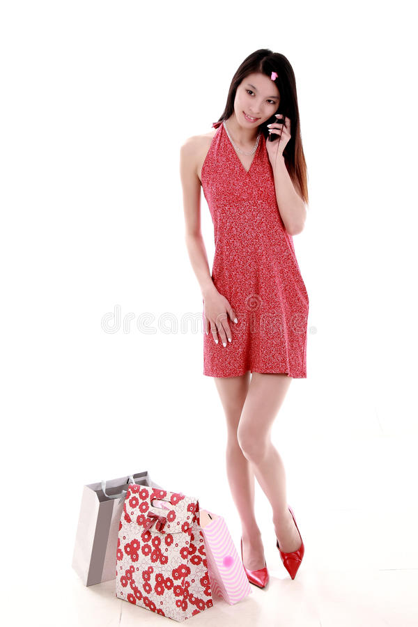 Asian shopping girl. A beautiful Asian girl holds a shopping bag on white background. She is phoning with the mobile phone royalty free stock image