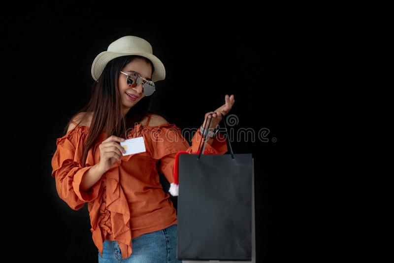 Asian shopping woman holding credit card with Black Friday shopping bag and Santa Claus hat inside on black background. royalty free stock photos