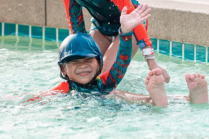Asian siblings swimming and chasing in Swimming pool royalty free stock photos