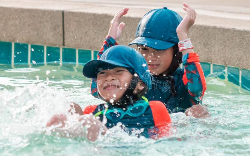 Asian siblings swimming and chasing in Swimming pool stock images