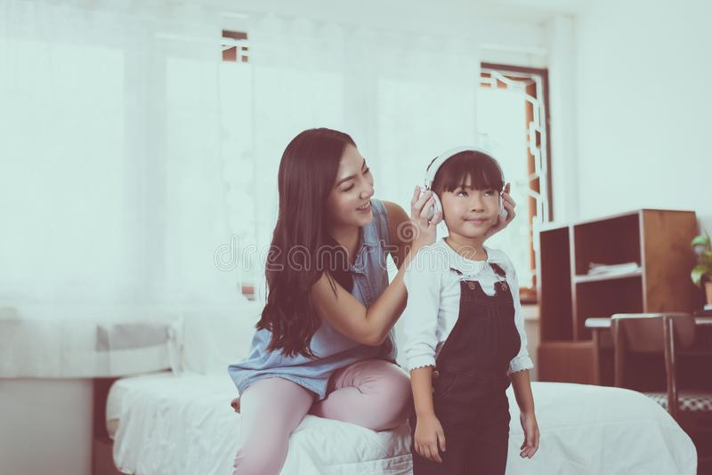 Asian single mom putting headphone to daughter at home,Happy and funny,Relaxing time royalty free stock photos