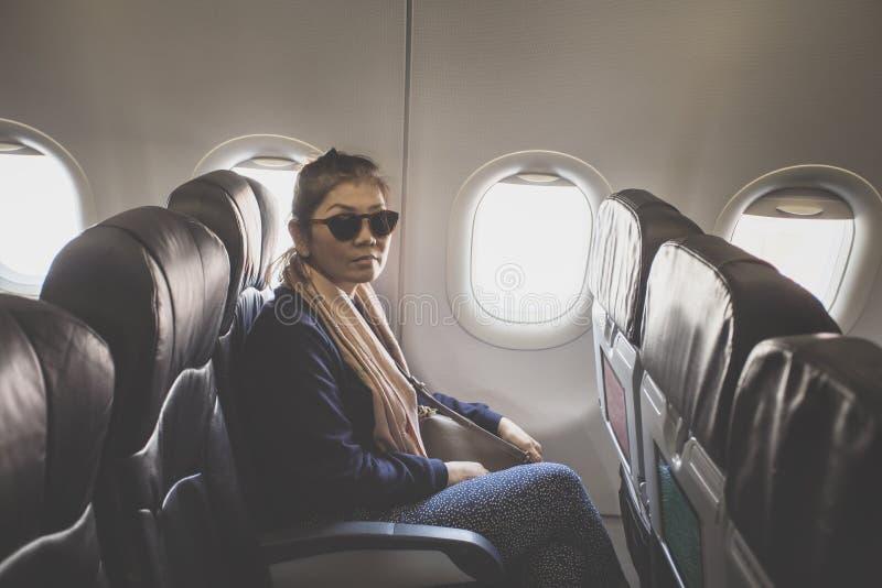 Asian single woman on passenger seat of airplane stock photos