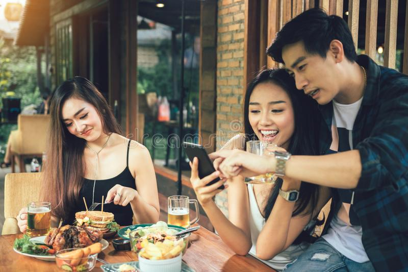 Asian single woman envious with love couple doing take selfie at restaurant stock photo