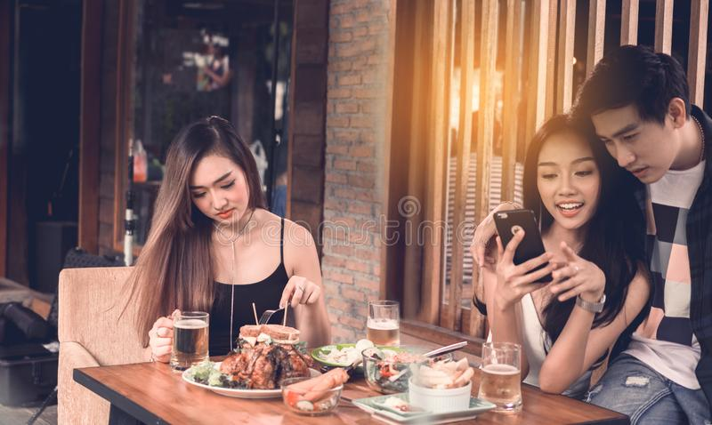 Asian single woman envious with love couple doing take selfie at stock photos
