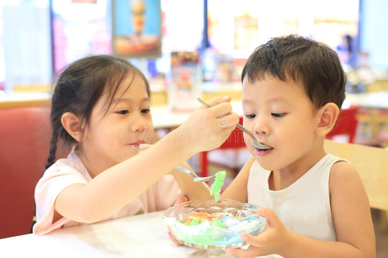 Asian sister and her little brother eating icecream together. Child girl feeding ice cream for baby boy in cafe royalty free stock photography