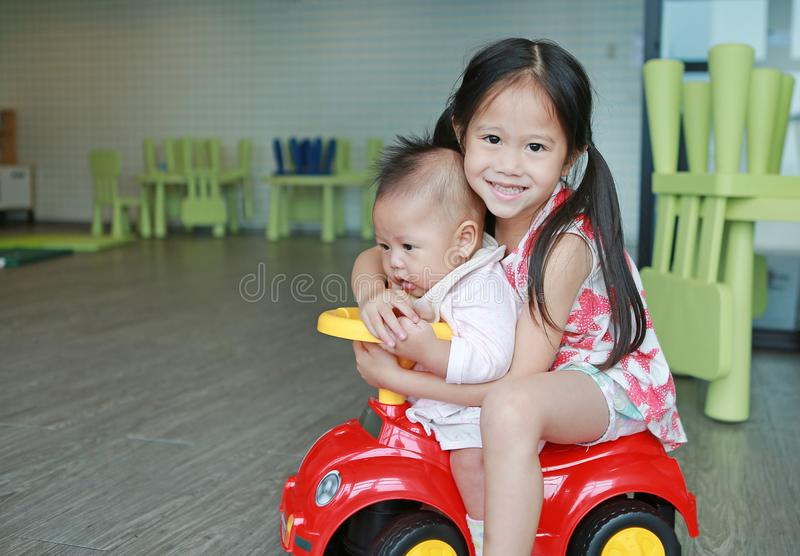 Asian Sister and little baby boy enjoying riding on a small toy car at playroom royalty free stock photography