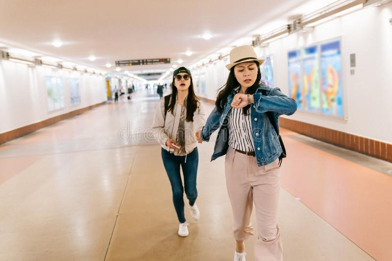 Asian sisters are in a rush to catch the train. Female travelers running in the passageway in the railway station. backpacker self-guided trip in USA concept royalty free stock photography