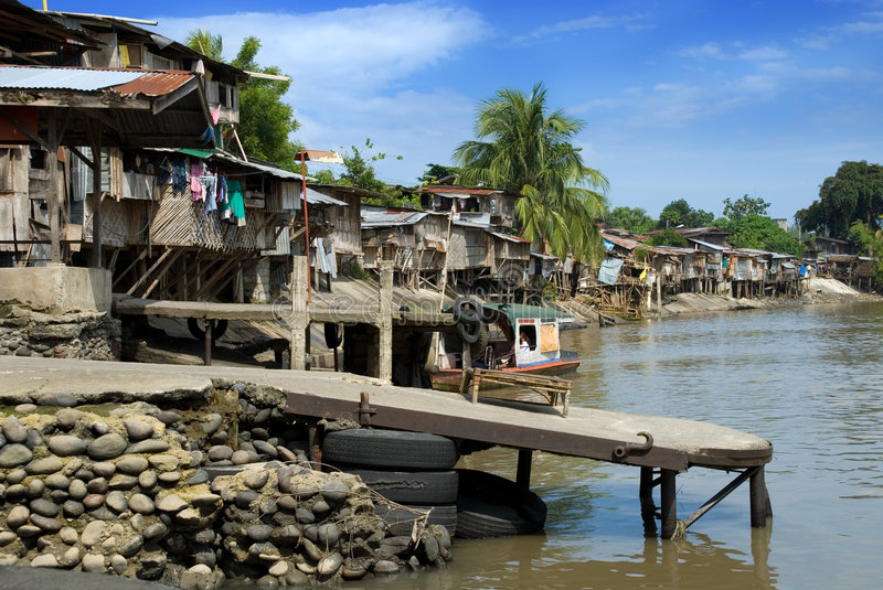 Asian slums on river bank. Asian slums, poor houses with clothesline, palm trees and jetty on a tropical muddy river bank royalty free stock photo