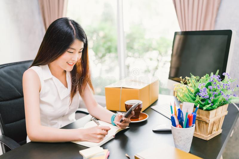 Asian small business owner work at home office, using mobile phone call, writing confirm purchase order on notebook. Young cute Asian small business owner work stock photography