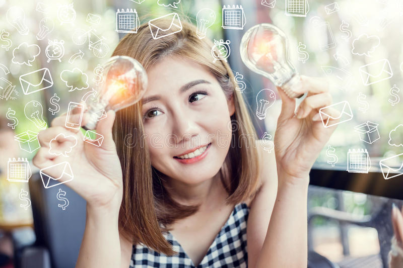 asian smart beauty girl with glow light bulb with drawing of light bulb in cafe creativity ideas concept stock photography