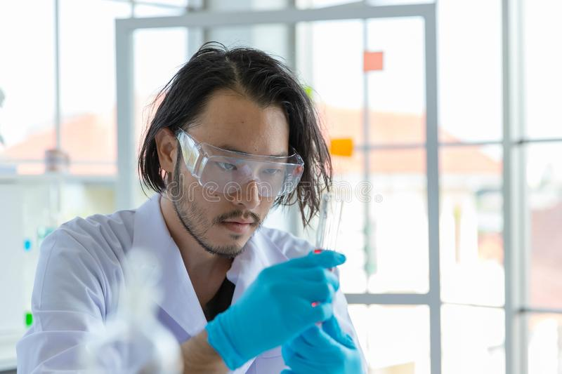 The Asian smart man scientist is testing test tube stock image