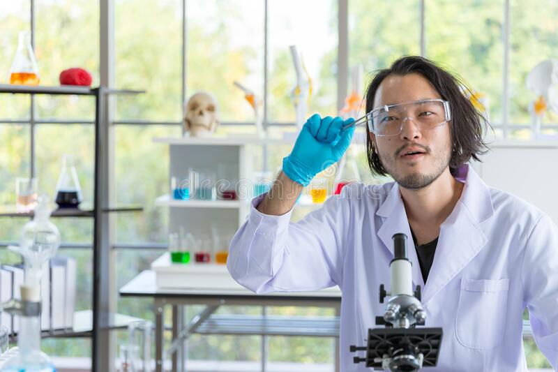 Asian smart pharmaceutical scientist feels amazed and happy with his new research product, tablet pill in research laboratory stock image