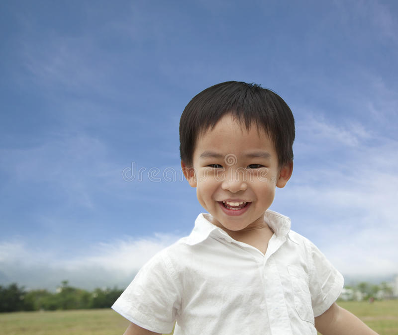 Asian smiling boy. Smiling boy with cloud background stock image