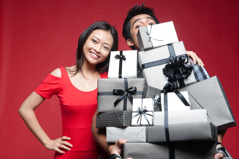 Asian Smiling Couple holding gifts stock image