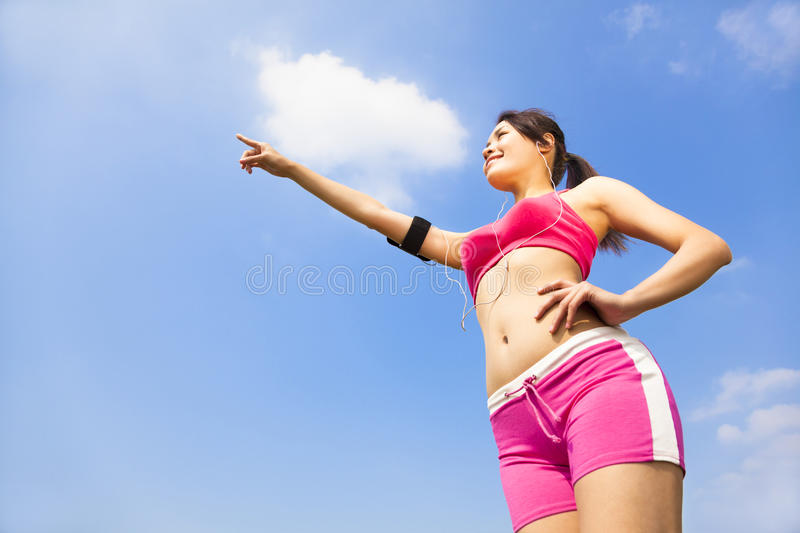 Download Asian Smiling Sporty Woman Watching And Pointing Far Away Stock Photo - Image: 37617248