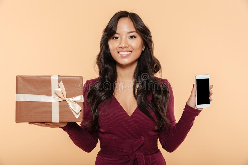 Asian smiling woman in maroon dress demonstrating present box wi. Th smartphone as gift, being isolated over peach background stock photography
