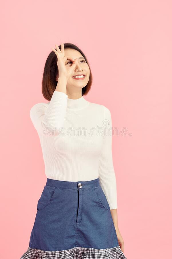 Asian smiling woman showing her hand with ok sign on her eye. Isolated on pink background.  stock photo