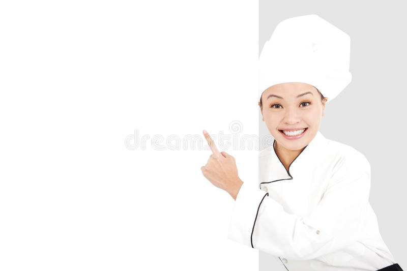 Asian smiling young woman chef pointing with blank board stock photos
