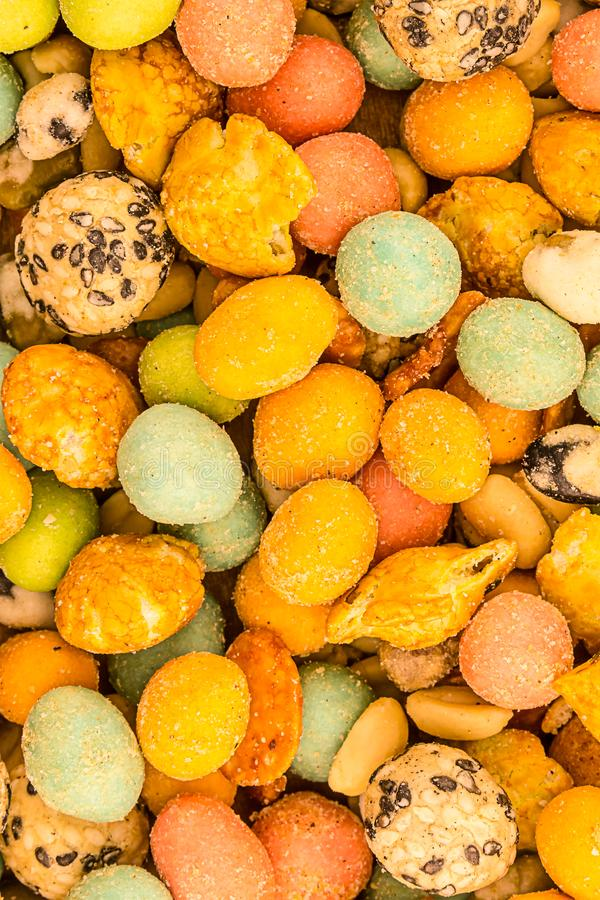 Asian snacks glazed sharp snack multicolored yellow pink dragee nut snack background edible design royalty free stock image