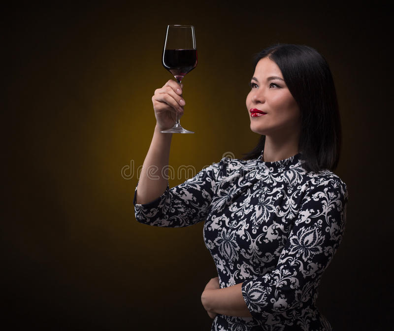 Asian sommelier woman with glass of red wine stock photo