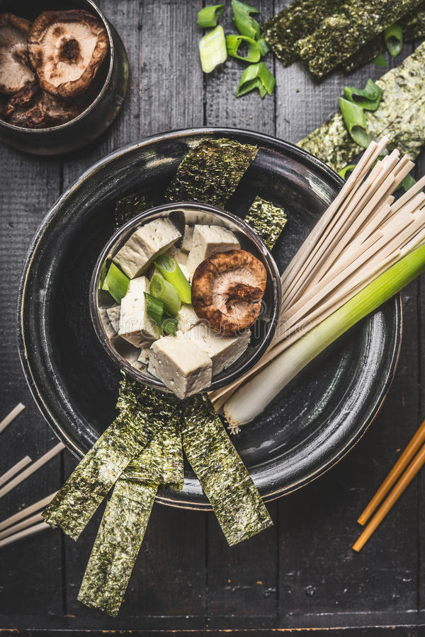 Download Asian Soup Preparation In Bowl With Udon Noodls, Tofu, Shiitake Mushrooms , Nori And Green Onion On Dark Rustic Background Stock Photo - Image: 83701846