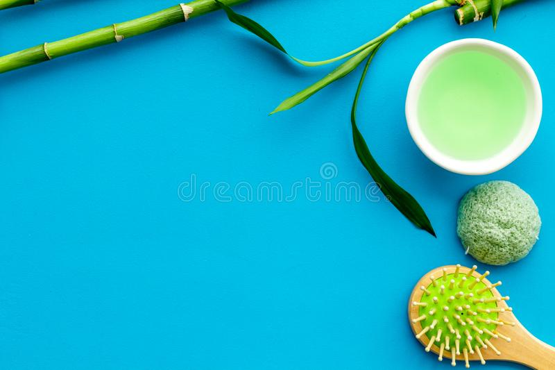 Asian spa treatment concept with natural ingredients. Spa salt, lotion, sponge near bamboo on blue background top view stock images