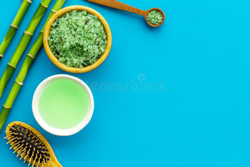 Asian spa treatment concept with natural ingredients. Spa salt, lotion, sponge near bamboo on blue background top view stock image